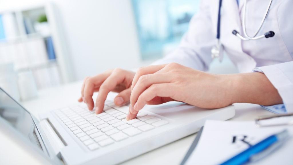 Bild på doktor som sitter vid en laptop.