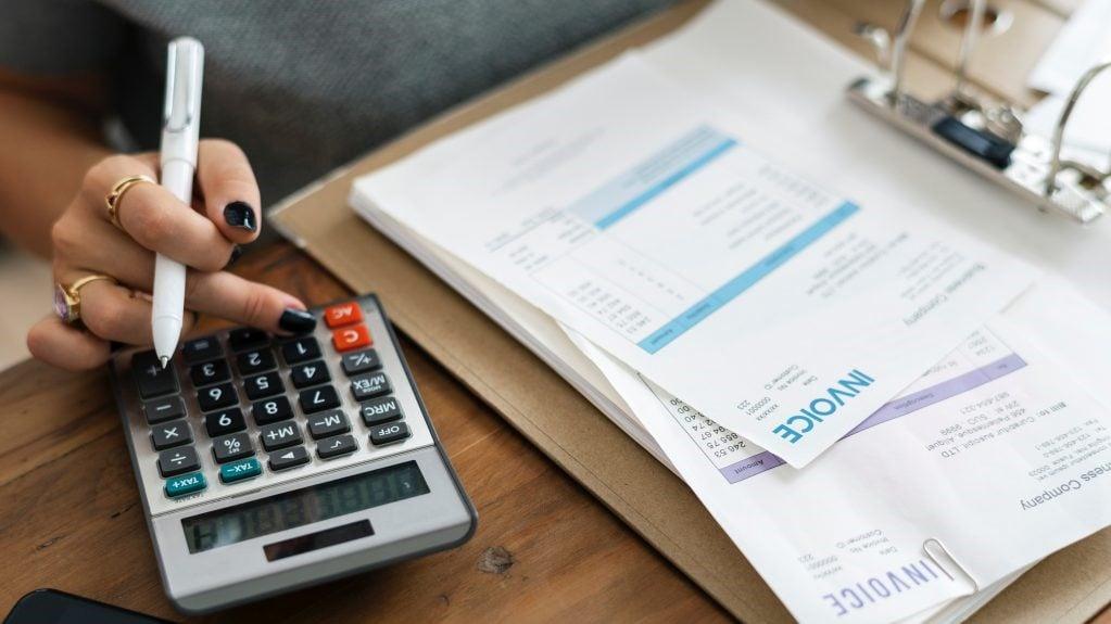 Foto av en hand som arbetar med en miniräknare vid sidan av en bunt fakturor.