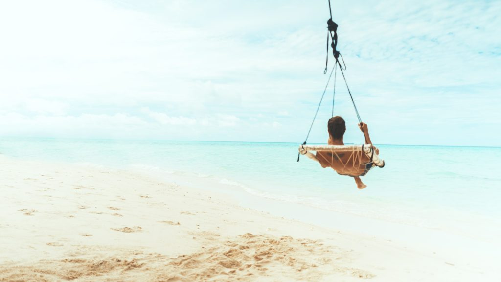 Bild på en strand med en person liggandes i en hängmatta.