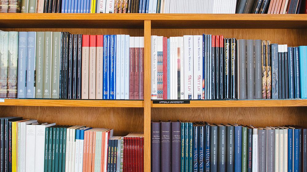 Foto på en välorganiserad bokhylla.