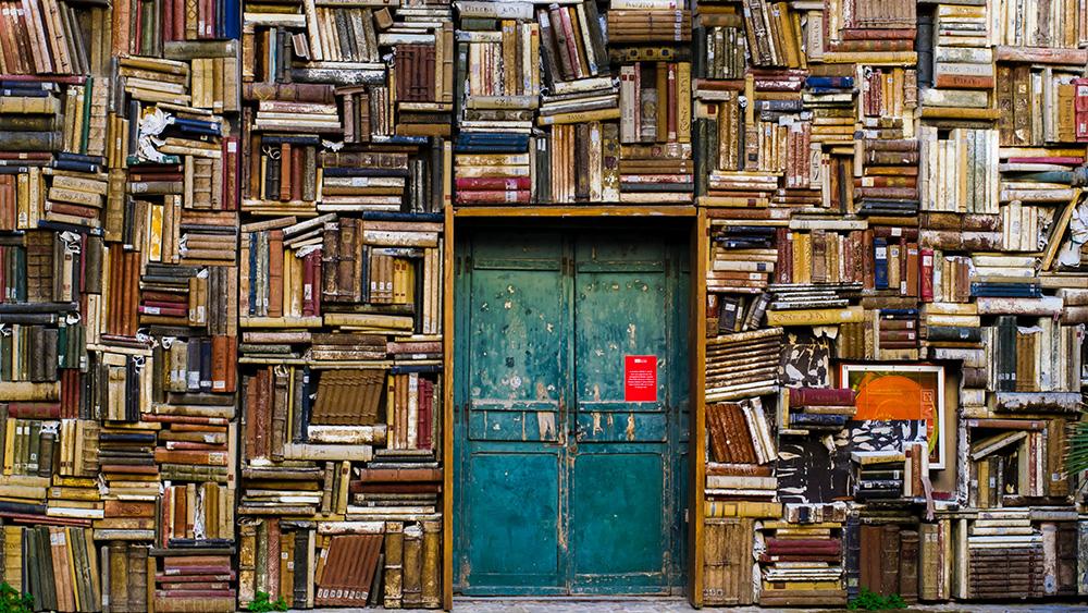 Foto på en väldigt rörig bokhylla.