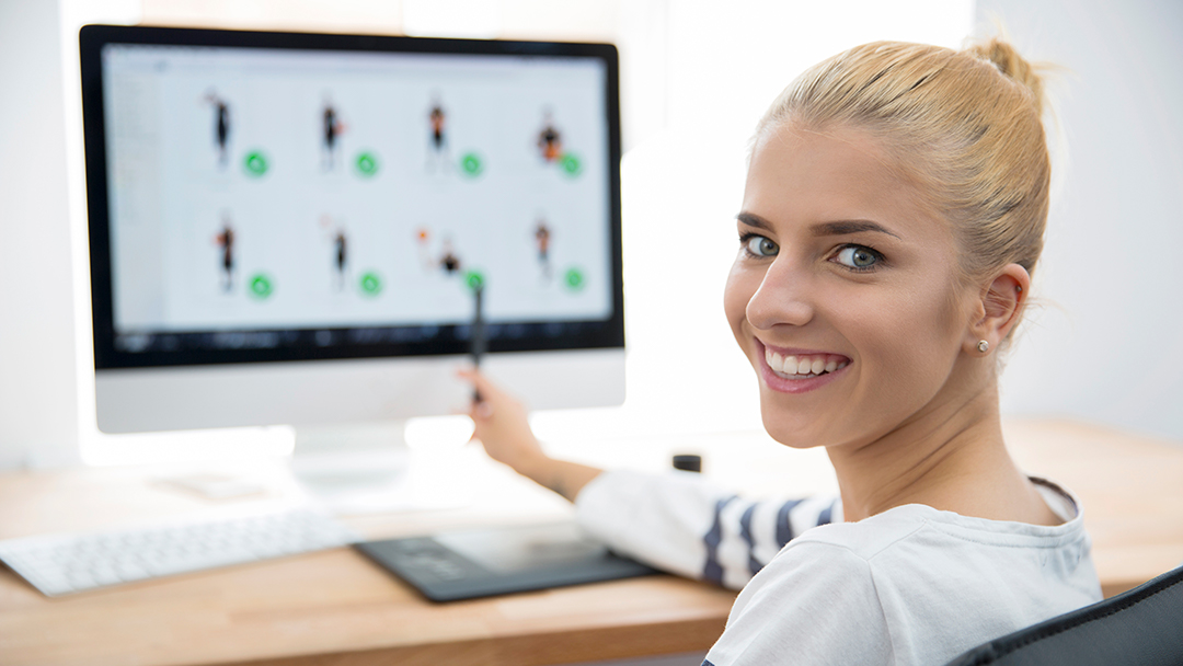A smiling girl sitting by a computer and pointing at the screen.